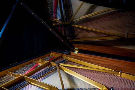 A close-up of the internal string structure of a top grand piano