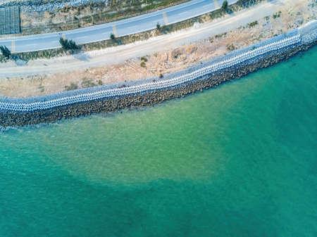 Cement block breakwater of coastal highway, aerial photography of highway seawall