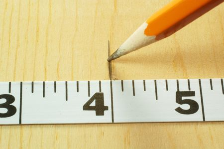 A pencil marks a measurement on a wood board Imagens - 490408