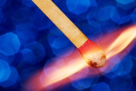 Matchstick catching fire on blue background  photo