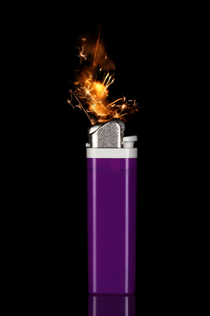 Purple cigarette lighter with sparks flame on black  Stock Photo - 23289628