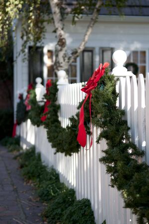 garland with red bows hanging on white picket fence photo