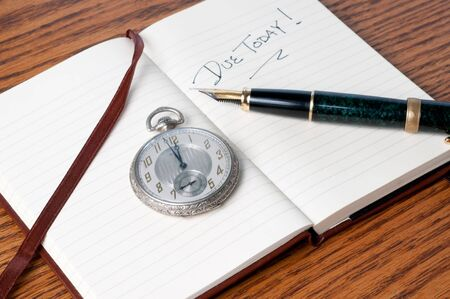 Antique pocket watch and fountain pen resting on open journal Stock Photo