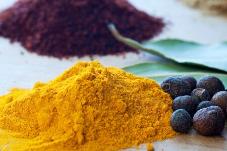 Closeup of tumeric powder and juniper berries with other spices in background