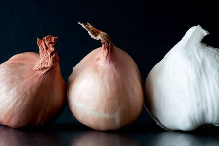 two shallot bulbs and one garlic bulb against dark background