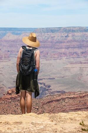 A hiker contemplates the view at the Grand Canyon in Arizona, USA