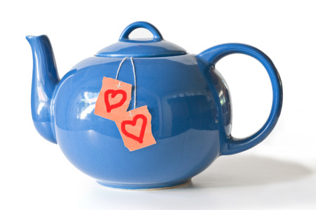 Blue tea pot containing teabags with heart symbols on isolated background