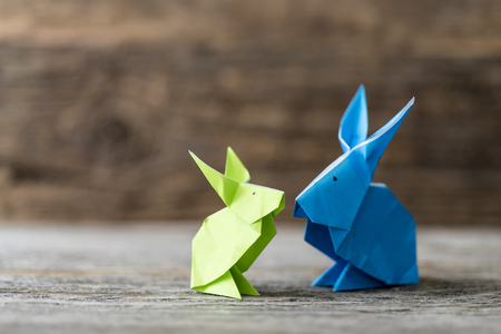 Two colorful origami Easter bunny rabbits made of paper in green and blue