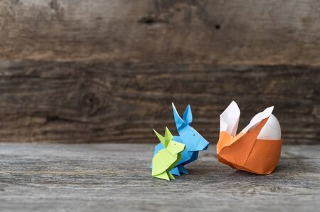 Three colorful origami Easter Bunny rabbits in green, blue, and orange made of paper, one stuffed with straw, cradling an egg for Easter or springtime, against rustic brown wood background Stock Photo