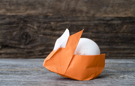 One colorful orange origami Easter Bunny rabbit basket made of paper stuffed with straw, cradling a white egg for Easter or springtime, against rustic brown wood background
