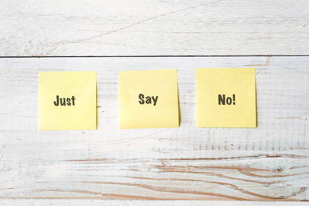three yellow Post It notes with message Just Say No! against weathered white wood background