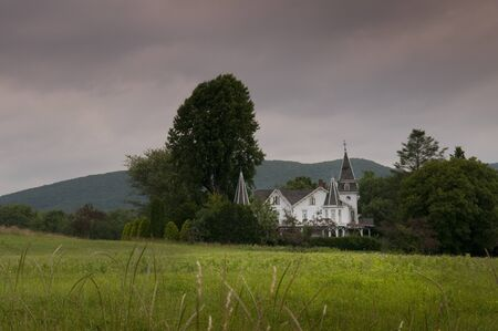 moody shot of gothic farm house isolated in green fields and trees set against stormy sky