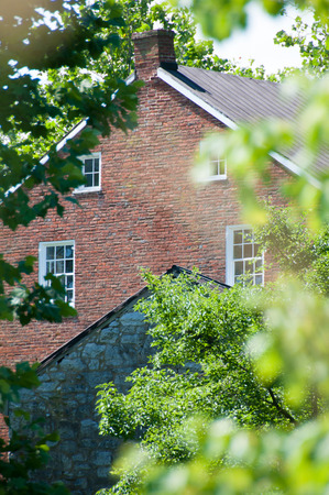 Red brick facade of a Pennsylannia farmhouse peaking through green summer foilage