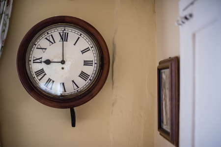 Old wooden clock, stopped at 9 o'clock, againt rough wall