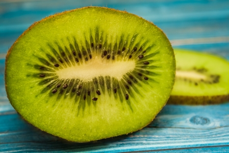 untruth: Juicy pieces of kiwi on a table, blue table Stock Photo