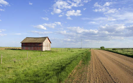 Farmers shed in the fields along side a gravel road photo