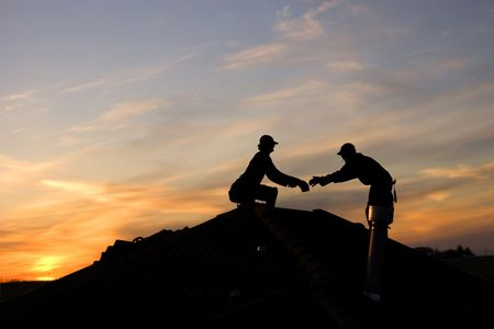 Two roofers working late on a roof top
