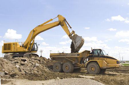 dump truck: A hoe filling up a dump truck Stock Photo