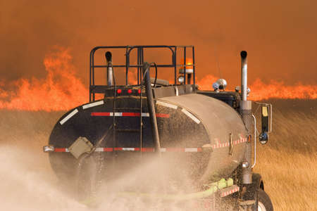 public insurance: A water truck helps to fight a large grass fire Stock Photo