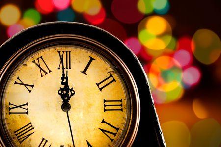 horloge ancienne: Juste avant minuit, � l'ancienne horloge avec les lumi�res en arri�re-plan