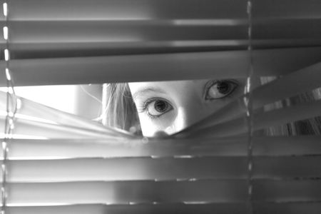 blinds: Young female looking through window blinds at night.(shallow depth of field)