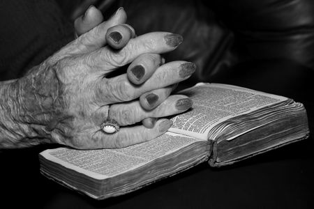Seniors Hands On Old Bible In Prayer Stock Photo