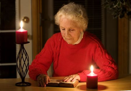 great grandmother: Elderly lady sitting in candlelight reading the bible Stock Photo