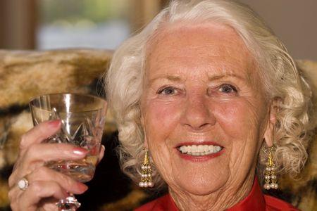 eighties: Beautiful elderly woman in her eighties enjoying a drink