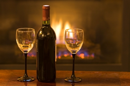 Bottle of wine with two empty glasses in front of a warm fire