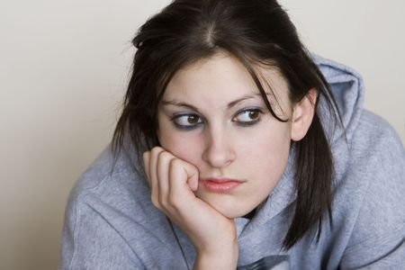 Bored teenager looking depressed, with a grey background