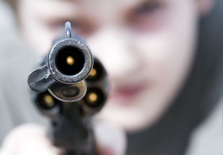 Loaded gun aimed at you, focus on gun barrel (shallow dof)