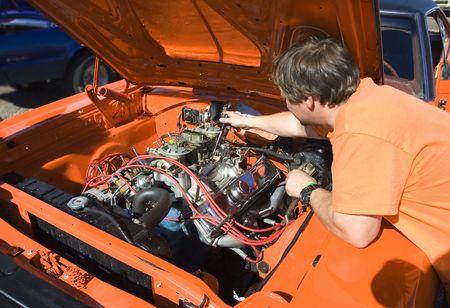 chrome man: mechanic tuning the carburetors on a classic muscle car