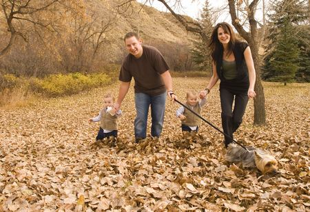 family running and playing through the leaves in Autumn