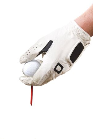 Isolated glove hand setting a golf ball
