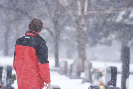 Man searching for a loved ones headstone during a snow storm Stock Photo - 852728