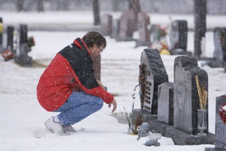 Man visiting a loved ones headstone in bad weather Stock Photo