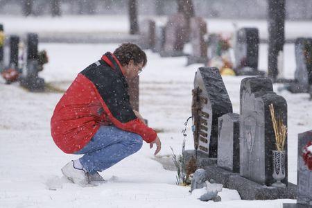 Man visiting a loved ones headstone in bad weather Zdjęcie Seryjne - 852726