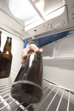 Man reaching into the fridge for a cool beer Zdjęcie Seryjne