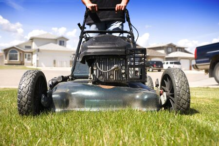 Close-up mowing the front lawn with houses in the background