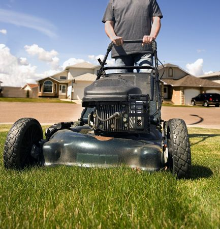 maintained: mowing the front lawn with houses in the background