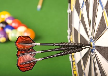 Three darts in a dart board with a pool game in the background, games room.