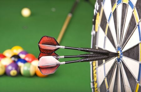 billiards room: darts in a dart board with a pool game in the background(shallow dof)