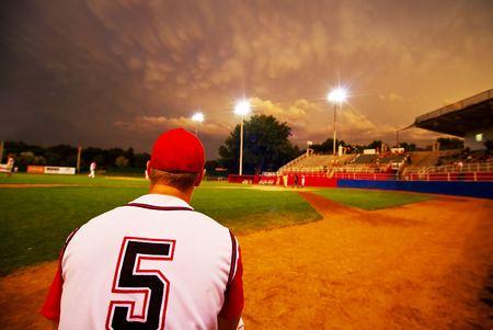 light game: Brocca sollievo guardando la sua squadra di baseball giocare di notte  Archivio Fotografico