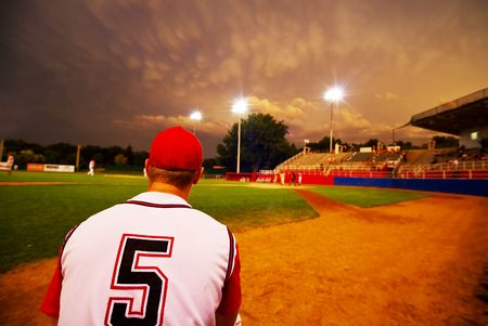 Relief pitcher watching his team play baseball at night