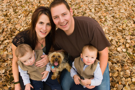 Young family with twin boys and pet dog in autumn leaves photo