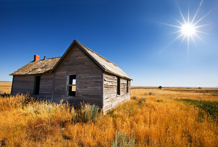 Old wooden home abandoned in the grasslands photo