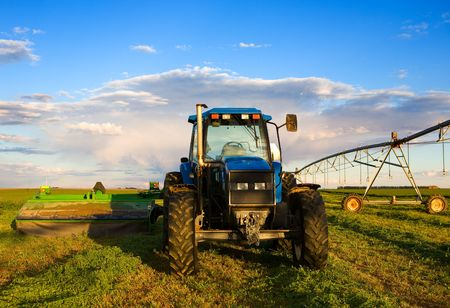 farm equipment: Farm equipment in the field with blue sky and clouds