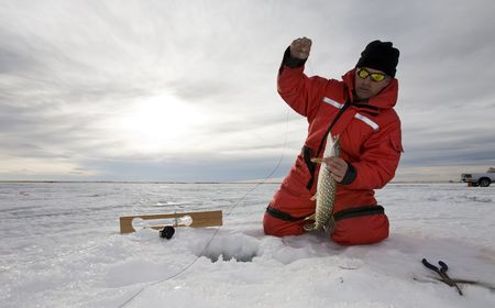 A man with a northern pike on a frozen lake Stockfoto