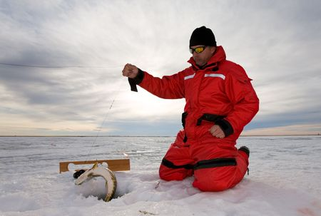 Ice fisherman catching a fish on a hand line