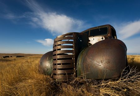 rusting: vintage truck abandoned and rusting away in the prairies, ghost town in the background